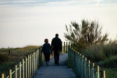 Middle-Aged Couple Walks on Boardwalk stock photos
