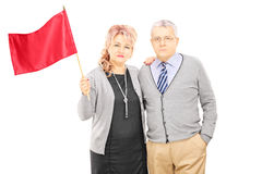 Middle aged couple waving a red flag Stock Photo
