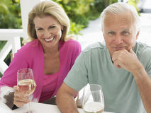 Middle Aged Couple With Wine At Outdoor Table Stock Images