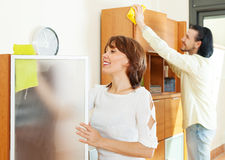 Middle-aged couple wiping the dust at home Stock Image