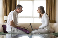 Middle aged couple working in their laptops Stock Photo