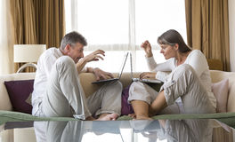 Middle aged couple working in their laptops Stock Photos