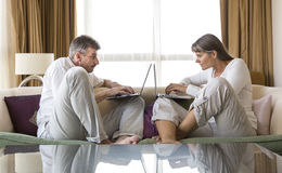Middle aged couple working in their laptops Stock Photography