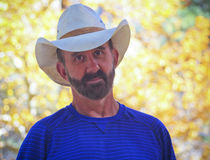 A Middle Aged Cowboy with Autumn Leaves Behind Stock Photo