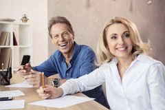 Middle aged coworkers sitting at business meeting and making notes. Smiling middle aged coworkers sitting at business meeting and making notes Stock Image