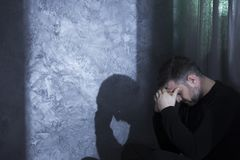 Middle-aged depressed man holding head. Middle-aged depressed man holding his head, fighting grief, next to marble wall Royalty Free Stock Photography