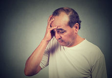 Middle aged desperate man isolated on gray wall background Stock Image