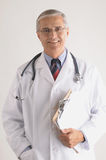 Middle Aged Doctor Holding a Clip Board Stock Image