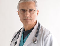 Middle aged Doctor in Labcoat with Stethoscope. Serious Middle aged Doctor in Scrubs and Labcoat with Stethoscope closeup Stock Photos