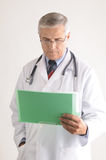 Middle Aged Doctor Looking at Patients Chart Stock Photo