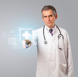 Middle aged doctor pressing modern medical button Stock Photography