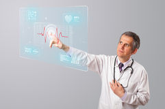 Middle aged doctor pressing modern medical type of button Stock Photo