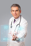 Middle aged doctor pressing modern medical type of button Royalty Free Stock Images