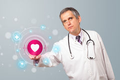 Middle aged doctor pressing modern medical type of button Royalty Free Stock Photos