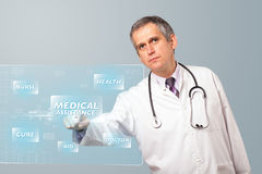 Middle aged doctor pressing modern medical type of button Royalty Free Stock Photography