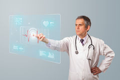 Middle aged doctor pressing modern medical type of button Royalty Free Stock Photo
