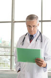 Middle aged doctor reading chart Stock Photo