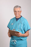 Middle aged Doctor in Scrubs with clipboard. Smiling Middle aged Doctor in Scrubs Reading a Patients cart on his clipboard Royalty Free Stock Images