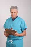 Middle aged Doctor in Scrubs with clipboard. Middle aged Doctor in Scrubs Reading a Patients cart on his clipboard Royalty Free Stock Images