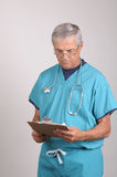 Middle aged Doctor in Scrubs with clipboard. Middle aged Doctor in Scrubs Reading a Patients cart on his clipboard Stock Photography