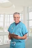 Middle aged Doctor in Scrubs with clipboard. Smiling middle aged doctor in scrubs holding a patients cart on his clipboard. Vertical composition in modern Royalty Free Stock Photo