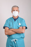 Middle aged Doctor in Scrubs Mask and Arms Folded. Middle aged Doctor in Scrubs with his arms folded wearing surgical mask Royalty Free Stock Photo