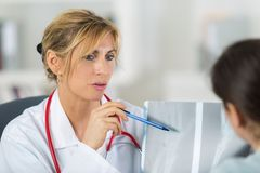 Middle aged doctor talking to patient. Middle stock photography