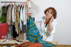 A middle-aged dressmaker talking on the phone Stock Photo