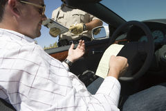 Middle Aged Driver Reading Ticket In Car. Middle aged driver reading ticket with traffic cop standing by his car Stock Photo