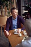 Middle aged elegant smiling have meeting in cafe. Enjoyable meetings. Waist up top angle portrait of mature elegant smiling male sitting in cafe and stock images