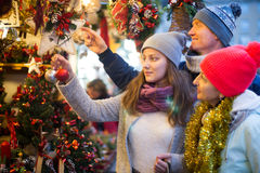 Middle-aged family couple with teen girl choosing Christmas deco. Ration at fair Royalty Free Stock Photography