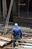 Middle aged fat woman working as a laborer stacking scaffolding pipe at building work site, a job fit for a man. San Pablo City, Laguna, Philippines - May 23 royalty free stock photo