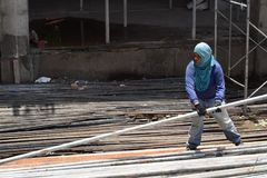 Middle aged fat woman working as a laborer stacking scaffolding pipe at building work site, a job fit for a man. San Pablo City, Laguna, Philippines - May 23 royalty free stock image