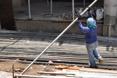Middle aged fat woman working as a laborer stacking scaffolding pipe at building work site, a job fit for a man. San Pablo City, Laguna, Philippines - May 23 stock photography