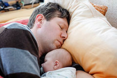 Middle aged father sleeping near his newborn baby daughter Stock Photos
