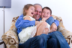 Middle-aged father with two laughing kids. Middle-aged father with two laughing young kids, a girl and boy, on his lap sitting in an armchair enjoying a moment Stock Photos
