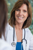 Middle Aged Female Doctor With Stethoscope. A happy smiling middle aged female doctor with a stethoscope sitting at a meeting with colleague in a hospital office Stock Photography