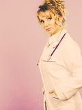 Middle aged female medical doctor. Female medical doctor in white professional uniform apron with blue stethoscope on her neck. Middle aged woman pharmacist Royalty Free Stock Photos