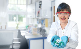 Middle-aged female scientist with handful of plastic tubes. Female scientist or tech smiless at the camera showing a handful of plastic tubes for medical samples royalty free stock photo