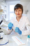 Middle-aged female scientist or tech looks at the camera with sa. Middle-aged female scientist or tech looks at the camera and shows a handful of plastic tubes Royalty Free Stock Photo