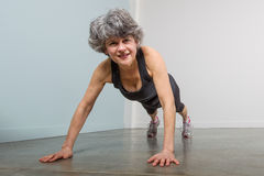 Middle Aged Female Sports Trainer in Pushup Position Royalty Free Stock Images