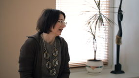 A middle-aged female teacher gives a lesson in design in a classroom stock footage