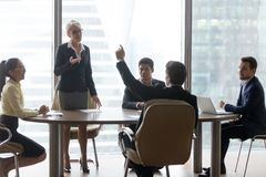 Diverse colleagues brainstorm at office business meeting. Middle aged female team leader stand listening to colleagues ideas at briefing, diverse employee stock image