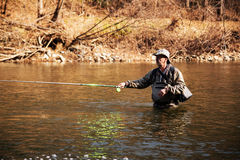 Middle-aged fisherman catching grayling in the river Royalty Free Stock Image