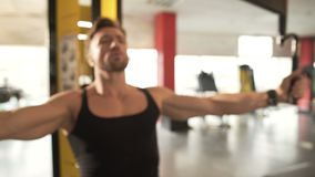 Middle-aged fit male doing pectoral fly workout in gym, training his arm muscles. Stock footage stock video