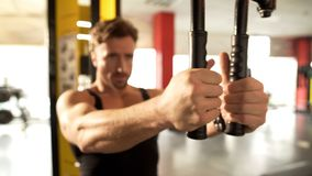 Middle-aged fit male doing pectoral fly workout in gym, training his arm muscles. Stock photo stock photo