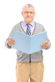 A middle aged gentleman holding a book and looking at camera Royalty Free Stock Photos
