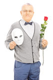 Middle aged gentleman holding rose flower and mask Stock Photography