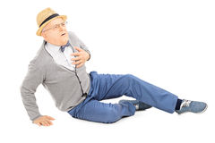 Middle aged gentleman laying on the ground having a heart attack Stock Image