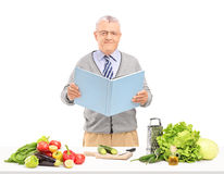 Middle aged gentleman reading a cookbook during a preparation of Stock Photos
